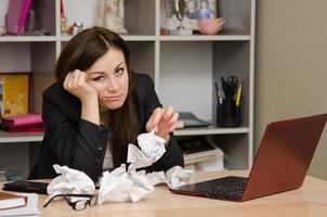 trauriges Mädchen im Büro mit einem Bündel zerknitterten Papiers foto