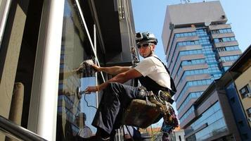 Mann, der Fenster an der Seite eines Bürogebäudes wäscht foto