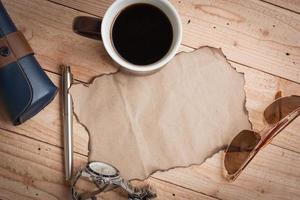 Sonnenbrille, Stift, Uhr, Grunge-Papier und Kaffee foto