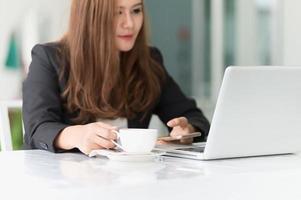 asiatische Frau im Café mit Laptop und Kaffee, Geschäftskonzept
