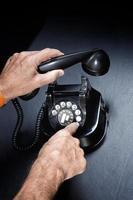 Mann hält das Vintage-Telefon hoch foto
