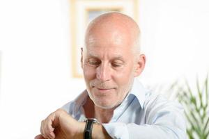 Mann schaut auf die Uhr foto