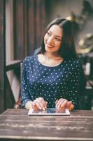schönes Mädchen, das an einer Tablette arbeitet und lächelt foto