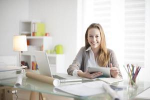 schöne junge Frau am Arbeitsplatz mit einem digitalen Tablet foto