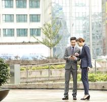 asiatischer Geschäftsmann und berufstätige Frau, die außerhalb der Bürotürme sprechen foto