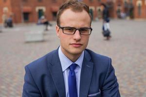 Porträt des jungen Geschäftsmannes, der vor Bürogebäude steht. foto