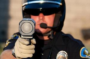 Polizist richtet eine Radarpistole auf die Kamera foto