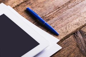 leere moderne digitale Tablette mit Papieren foto