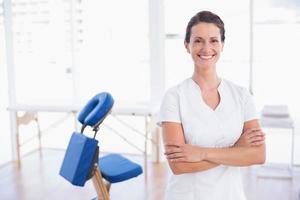 lächelnder Therapeut, der mit verschränkten Armen steht foto