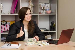 hübsches junges Mädchen, das mit Haufen Geld am Schreibtisch sitzt foto
