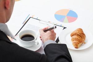 Kaffee und Croissant während der Arbeit foto