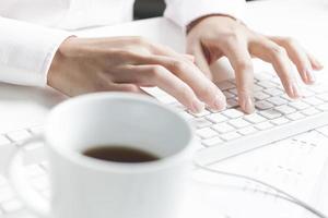 Frau, die auf Tastatur, Kaffeetasse tippt