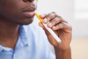 Geschäftsmann, der eine elektronische Zigarette raucht foto