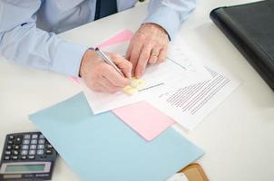 Geschäftsmann nimmt eine Notiz auf einem Post it foto