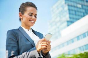 glückliche Geschäftsfrau, die SMS vor Bürogebäude schreibt foto