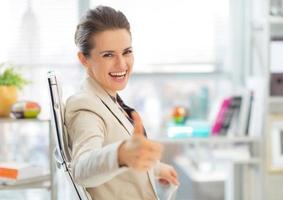 glückliche Geschäftsfrau, die Daumen hoch zeigt