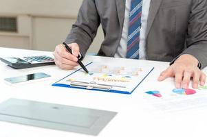 Geschäftsmann, der Bericht, Geschäftsleistungskonzept analysiert foto