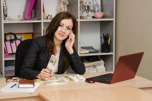 Geschäftsfrau an einem Schreibtisch mit Stapel Geld foto
