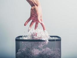 Hand, die zerkleinertes Papier in den Korb legt