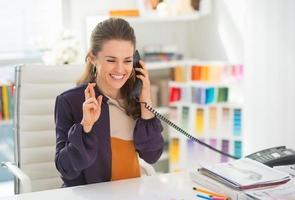 glücklicher Modedesigner, der Telefon mit gekreuzten Fingern spricht foto