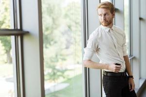erfolgreicher Geschäftsmann, der am Fenster steht foto