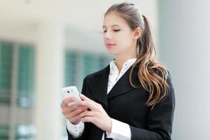 Geschäftsfrau, die eine SMS sendet foto