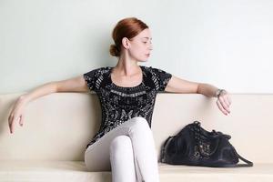 junge Frau sitzt und schaut auf ihre Uhr foto