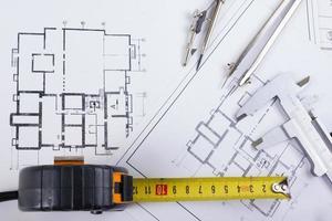 Architekturprojekt, Blaupausen, Teilerkompass, Bremssättel, Bleistift, Taschenrechner auf Plänen foto