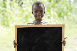 junger afrikanischer Junge, der Tafel draußen für ein Kommunikationssymbol hält foto