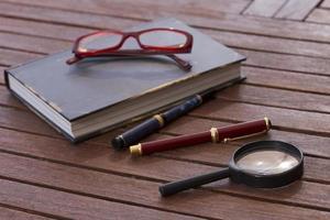 geschlossenes Buch, rote Brille, Füllfederhalter und Kugelschreiber