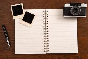 leeres Notizbuch mit Stift, Bilderrahmen und Kamera foto