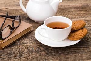 Teetasse, Keks, Gläser und Buch foto