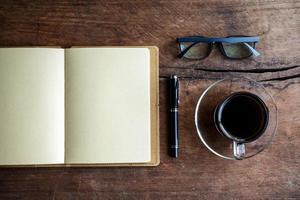 Tasse Kaffee mit Notizbuch auf altem Holz foto