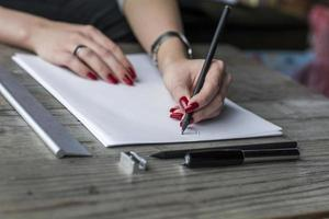 Frauenhand, die auf weißes Papier schreibt foto