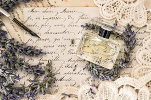 Parfüm, Lavendelblüten, Vintage Tintenschreiber und alte Liebesbriefe foto