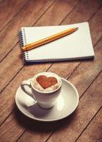 Tasse Kaffee mit Notizbuch auf einem Holztisch.