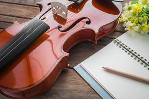 Nahaufnahme von Geige und Buch auf Holztisch