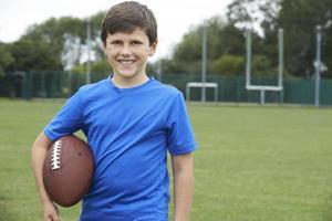 Porträt des Jungen, der Ball auf Schulfußballplatz hält foto