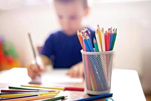 Junge, der ein Bild zeichnet, Bleistifte im Fokus foto