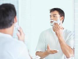 Morgenroutine - reifer Mann, der sich vor dem Spiegel rasiert foto