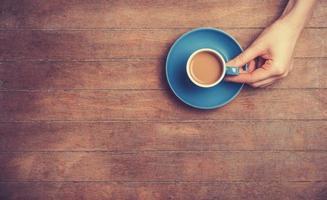weibliche Hände, die Tasse Kaffee halten.