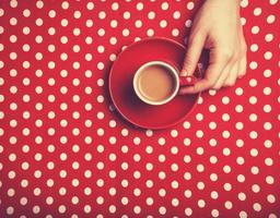 weibliche Hand, die Tasse Kaffee hält.