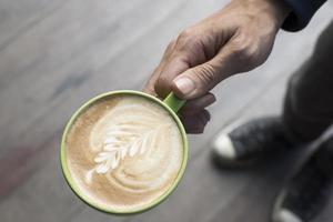 Hand hält eine Tasse Kaffee foto