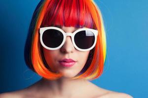 schöne Frau, die bunte Perücke und weiße Sonnenbrille gegen trägt foto
