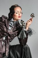Frau spricht am Retro-Telefon foto