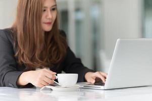 asiatische Frau im Café mit Laptop und Kaffee, Geschäftskonzept foto