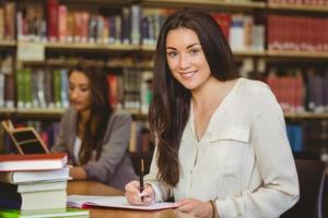 lächelnder hübscher brünetter Student, der im Notizblock schreibt foto