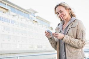 lächelnde Blondine stehend und SMS foto