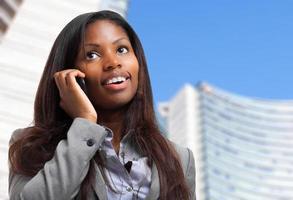 schwarze Geschäftsfrau, die am Telefon spricht foto