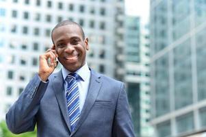 lächelnder Geschäftsmann, der am Telefon spricht